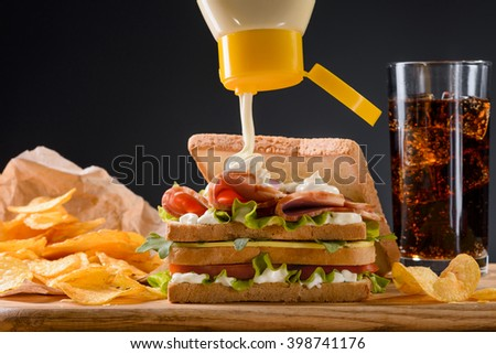 Pouring mayonnaise on sandwich with meat, cheese and vegetables. Scattered chips on wooden desk. Icy cola with bubbles. Dark background. American fast food.