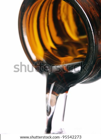 Pouring medicine syrup detail on white background.