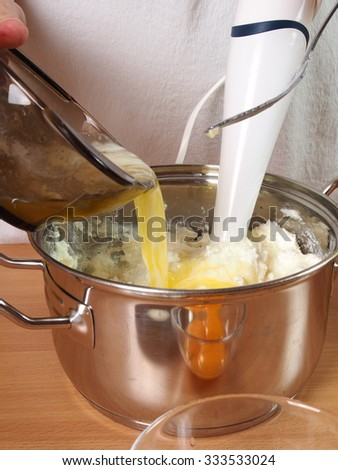 Pouring melted butter into cheese cream. Making Chocolate Layer Cake with Cream Cheese Filling and Chocolate Topping. Series. #333533024