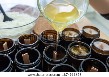 Pouring melted wax. Handmade soy candles with mica and wooden wick. Amber and opaque container. Vegan product without animal cruelty.