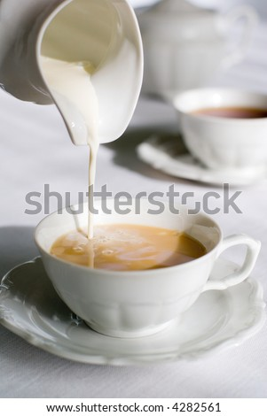Pouring milk from porcelain milk jug into cup filled with tea.