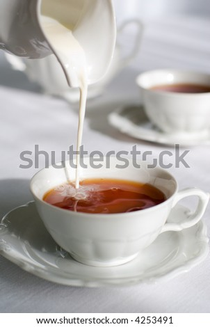 Pouring milk from porcelain milk jug into cup filled with tea - white tablecloth background.