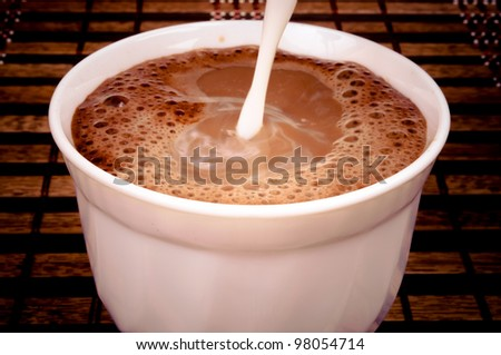 Pouring milk in the coffee - stock photo