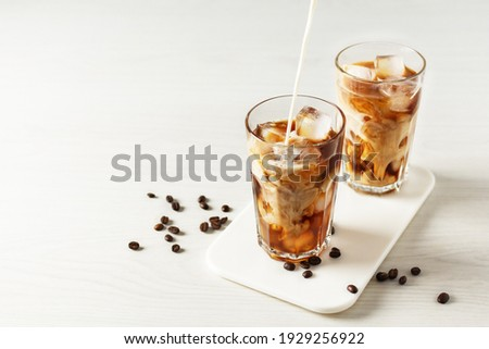 Pouring milk into glass with iced coffee. Cold refreshment summer drink.