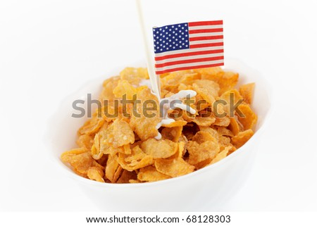 pouring milk over corn flakes in a bowl isolated on white