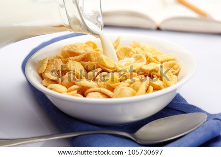 Pouring milk over cornflakes #105730697