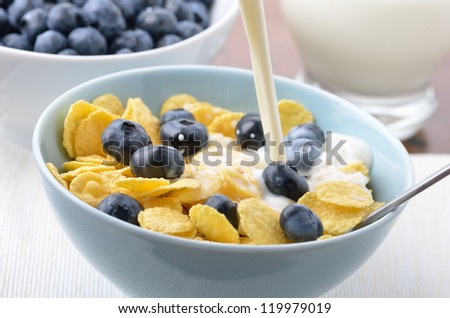 Pouring milk over cornflakes and blueberries
