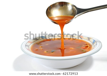 Pouring minestrone soup into a bowl with a ladle isolated on white