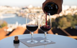 Pouring of fortified dessert ruby, tawny port wines in glasses with view on Douro river, porto lodges of Vila Nova de Gaia and city of Porto, Portugal, on sunset