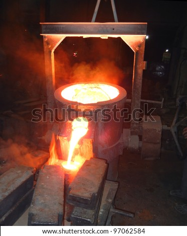 Pouring of liquid metal. Iron and steel industry. Foundry - molten metal poured from ladle