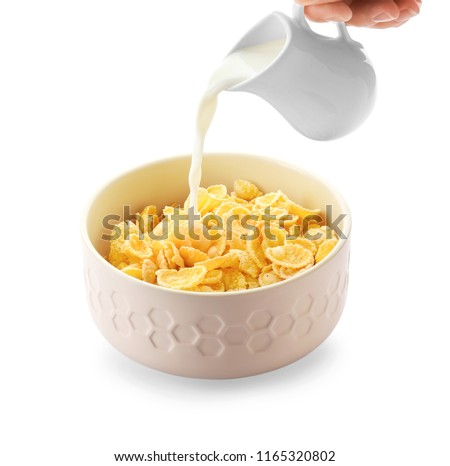 Pouring of milk into bowl with healthy cornflakes on white background #1165320802