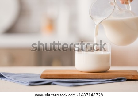Pouring of milk into glass on table Photo stock ©