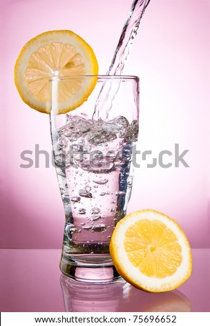 Pouring of mineral water in glass with a lemon on a pink background