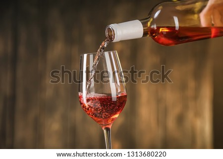 Pouring of red wine from bottle into glass on dark background #1313680220