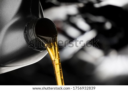 Pouring oil lubricant motor car from black bottle on engine background oil change auto shop Stock fotó ©