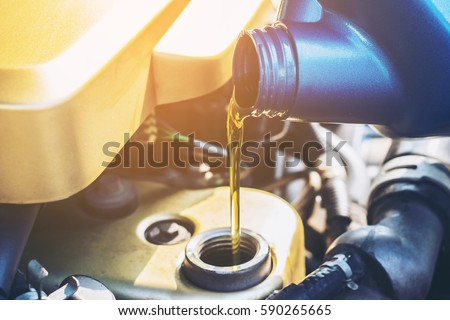 Pouring oil to car engine, close up selective focus