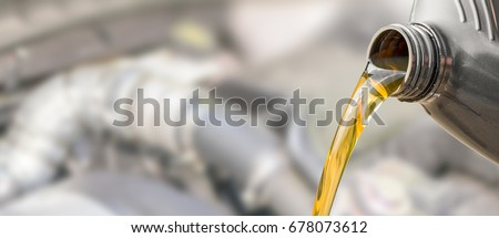 Pouring oil to car engine. Fresh oil poured during an oil change to a car.