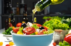 Pouring Olive oil on fresh Vegetable salad, mediterranean cuisine, Greek salad, white table served with healthy food ingredients