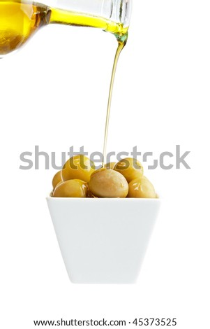 Pouring olive oil on olives isolated on a white background. Shallow depth of field