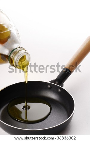 Pouring olive oil over a pan.