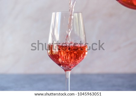 Pouring Pink Rose Blush Wine to Glass #1045963051