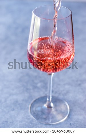 Pouring Pink Rose Blush Wine to Glass #1045963087