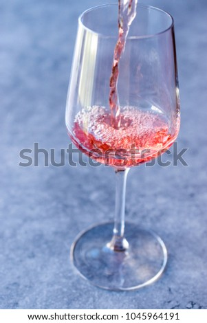 Pouring Pink Rose Blush Wine to Glass #1045964191