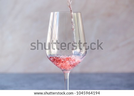 Pouring Pink Rose Blush Wine to Glass #1045964194