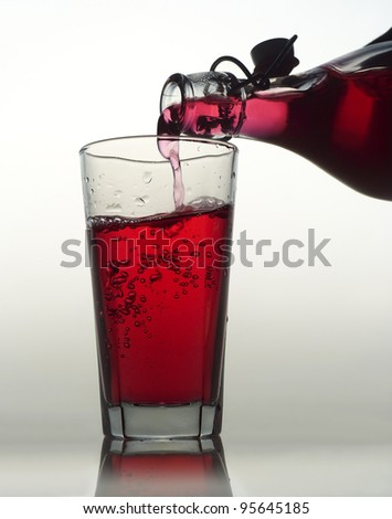 Pouring Red Lemonade in a glass on white background