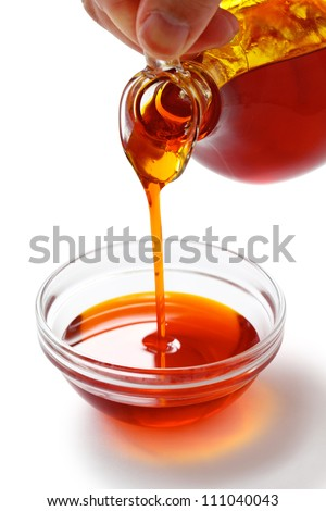 pouring red palm oil into a glass bowl