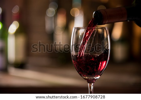 pouring red wine from bottle into glass bokeh background ストックフォト ©