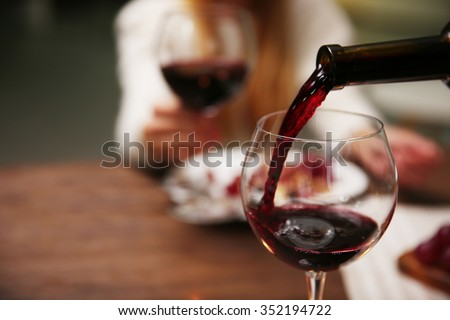 Pouring red wine from bottle into the wineglass #352194722