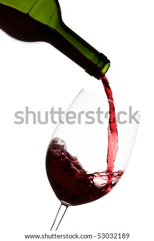 Pouring red wine into a crystal wine glass over white background