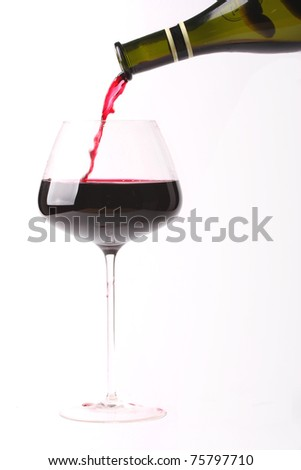Pouring red wine into a large, fancy glass. Isolated on white background.