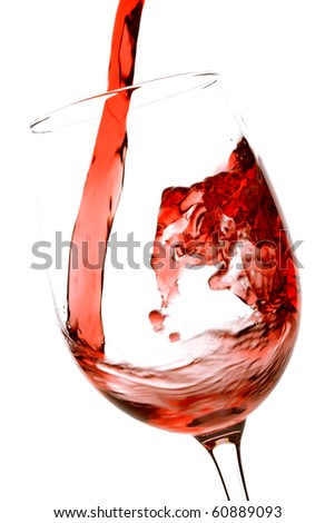 Pouring red wine into a wine glass over white background