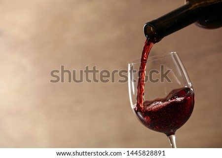 Pouring red wine into glass from bottle against blurred beige background, closeup. Space for text #1445828891