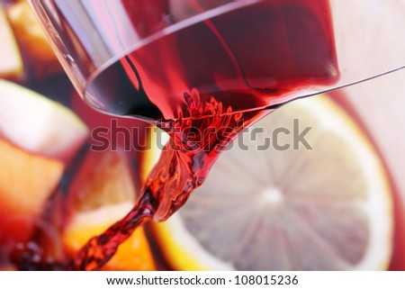 Pouring red wine into juice fruits