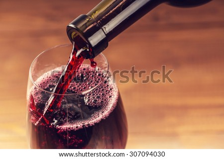 Pouring red wine into the glass against wooden background #307094030