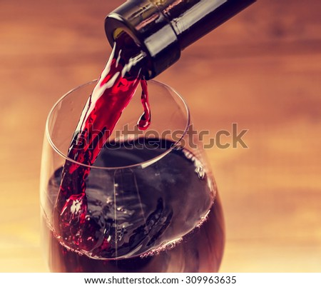 Pouring red wine into the glass against wooden background #309963635