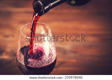 Pouring red wine into the glass against wooden background #370978040