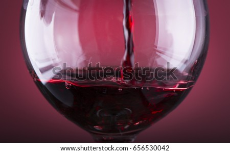 Pouring red wine into the glass against wooden background #656530042