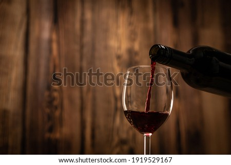 Pouring red wine into the glass against wooden blurred background. Foto d'archivio ©