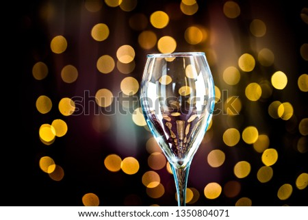 Pouring red wine into the glass. Golden bokeh background. #1350804071