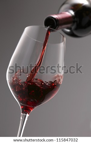 Pouring red wine into the wine glass