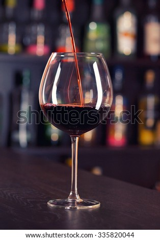 Pouring red wine on a bar counter #335820044