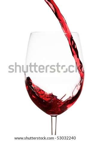 Pouring red wine splashes into a crystal wine glass