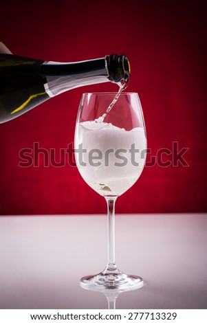 Pouring sparkling wine in a glass; preparing spritz; wine-based long drink, slightly alcoholic.