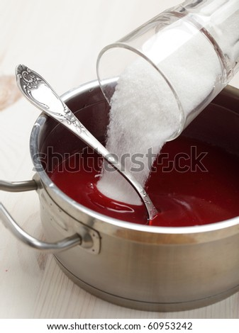Pouring sugar into the red currant syrup