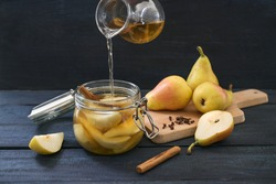 Pouring syrup in a glass jar with sliced pear, cinnamon and cloves to preserve summer fruits for the winter time, dark wooden table, copy space, selected focus, narrow depth of field and motion blur