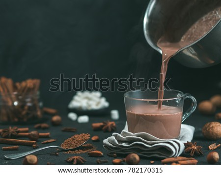 Pouring tasty hot chocolate cocoa drink into glass mug with ingredients on black table. Copy space Dark background. Low key. #782170315